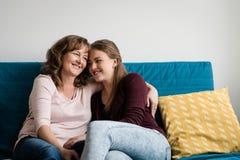 拥抱她充满爱的母亲青少年的女儿 免版税库存照片