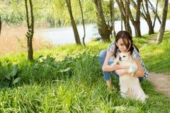 拥抱她微小的狗的可爱的妇女 免版税库存照片