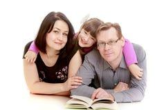 拥抱她心爱的父母的逗人喜爱的女孩 库存图片