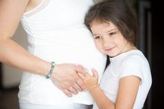 拥抱她怀孕的母亲腹部的逗人喜爱的小女孩 免版税图库摄影