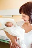 拥抱她新出生的婴孩的爱恋的母亲 库存图片
