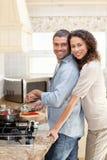 拥抱她的丈夫的妇女,当他烹调时 库存图片