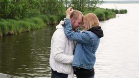 拥抱她的丈夫的孕妇反对湖的背景 预期儿童进来的年轻家庭 股票录像