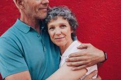 拥抱她的丈夫的愉快的成熟妇女 免版税库存图片