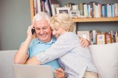 拥抱她的丈夫的激动的资深妇女,当使用膝上型计算机时 免版税库存照片