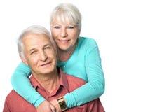 拥抱她的丈夫的资深妇女 免版税库存照片