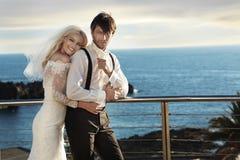 拥抱她的丈夫的逗人喜爱的年轻新娘 免版税库存图片