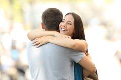 拥抱她的伙伴的愉快的女朋友在遭遇以后 免版税库存照片