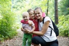 拥抱她的儿子和女儿的致力的母亲,享用室外 免版税库存图片