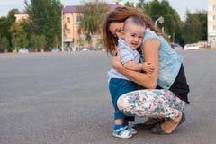 拥抱她的儿子的美丽的母亲 免版税库存图片