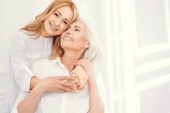 拥抱她的充满爱的嫩成熟妇女资深妈妈 免版税库存照片