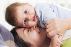 拥抱她的充满喜爱的快乐的母亲男婴。 免版税库存图片