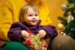 拥抱她的在圣诞礼物和装饰的新年树的愉快的祖母画象孙女,快活 库存图片