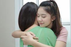 拥抱她的在母亲da的十几岁的女孩妈妈,愉快和爱家庭 库存图片