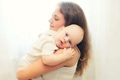拥抱她的在白色窗口的画象爱恋的母亲婴孩 库存照片