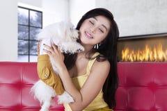 拥抱她的在长沙发的可爱的女孩小狗 免版税库存照片