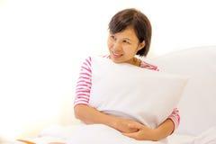 拥抱她的坐垫的轻松的妇女坐她的床 免版税图库摄影