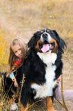 拥抱她的大狗的愉快的女孩 免版税库存照片