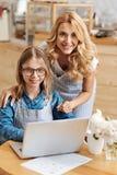 拥抱她的女儿的爱恋的母亲研究膝上型计算机 库存照片
