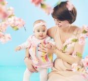 拥抱她的女儿的笑的妈妈 免版税库存图片