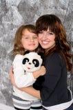 拥抱她的女儿的年轻母亲户内 免版税库存图片