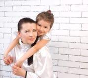 拥抱她的妈妈的一件白色礼服的女儿 免版税库存图片