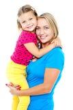 拥抱她的妈妈的逗人喜爱的女儿。 偶然射击 库存图片