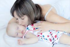 拥抱她的婴儿的年轻母亲 妈妈护理婴孩 免版税库存图片