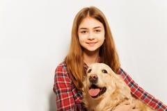 拥抱她的宠物的美丽的十几岁的女孩 免版税库存照片