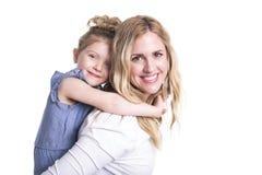 拥抱她的小女儿的年轻母亲隔绝在白色 库存图片