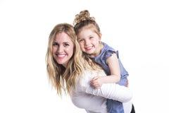 拥抱她的小女儿的年轻母亲隔绝在白色 图库摄影