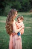 拥抱她的小小孩儿子的年轻美丽的母亲反对绿草 有她的男婴的愉快的妇女在一个夏天 库存照片