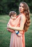拥抱她的小小孩儿子的年轻美丽的母亲反对绿草 有她的男婴的愉快的妇女在一个夏天 免版税库存照片