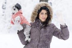 拥抱她的小白色狗的美丽的少妇在冬天森林里 挥动的你好 库存照片
