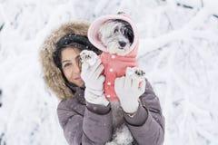 拥抱她的小白色狗的美丽的少妇在冬天森林里 降雪的时间 免版税库存图片