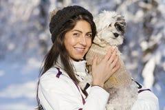 拥抱她的小白色狗的美丽的少妇在冬天森林里 降雪的时间 免版税库存照片