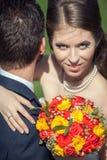 拥抱她的有花束的妻子丈夫在手上 免版税库存照片