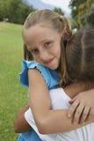 拥抱她的朋友的逗人喜爱的女孩 免版税库存照片