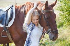 拥抱她的棕色马的美丽的白肤金发的女孩 在温暖的口气的夏天照片 库存照片