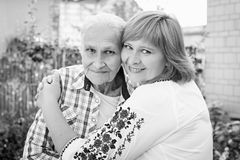 拥抱她的母亲本质上的中年妇女 幸福的真正的情感 日花产生母亲妈咪儿子 北京,中国黑白照片 免版税库存照片