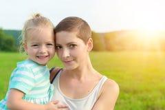 拥抱她的母亲的可爱的女孩 免版税库存图片