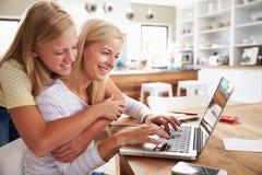 拥抱她的母亲的女孩,在家研究膝上型计算机 免版税库存图片