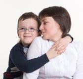 拥抱她的母亲的肩膀的玻璃的儿子 库存照片