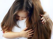 拥抱她的母亲的脖子的小逗人喜爱的女孩 免版税图库摄影