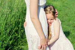 拥抱她的母亲的逗人喜爱的小女孩 免版税库存图片
