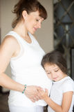拥抱她的母亲腹部的逗人喜爱的小女孩 免版税库存照片