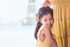 拥抱她的母亲腿的哀伤的亚裔儿童女孩 免版税库存照片