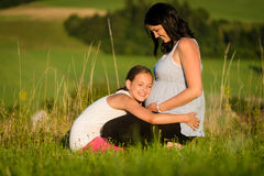 拥抱她的母亲` s怀孕的腹部的女儿 免版税库存照片