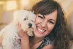 拥抱她的爱犬的愉快的微笑的妇女 免版税库存图片
