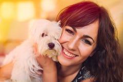 拥抱她的爱犬的美丽的愉快的妇女 图库摄影